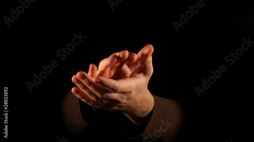 Clapping hands on black background