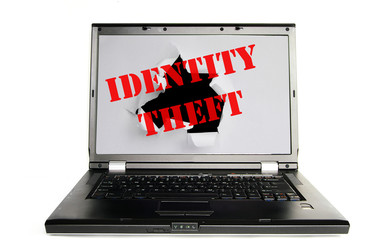 Laptop with a hole torn and Identity Theft text