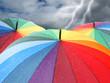 Rainbow umbrellas on dramatic sky background