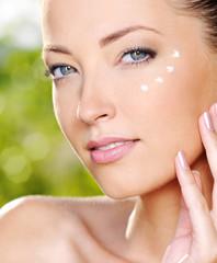 Beautiful woman applying cream near eyes