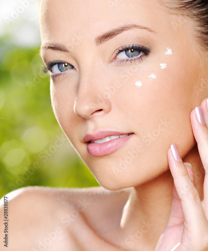 Beautiful woman applying cream near eyes