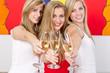 drei blonde frauen stoßen mit sekt an