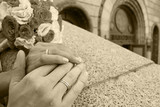 Hands of the groom and the bride on a handrail. Sepia poster