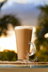 coffee latte in palm tree and sunset background