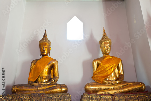 two buddha in front of small window