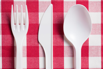 plastic cutlery on checkered tablecloth
