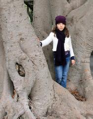 Bambina appoggiata alla base di una pianta secolare