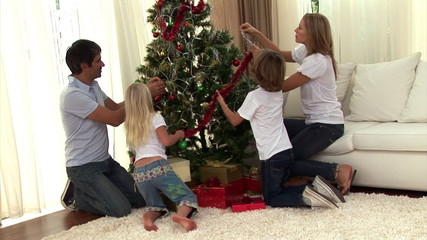 Montage of a family decorating a christmas tree