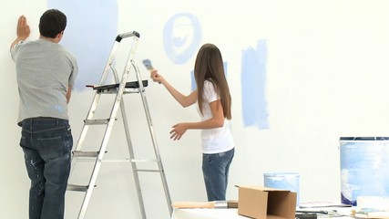 Young couple having fun while painting walls