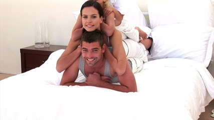 Adorable family is playing together on the bed