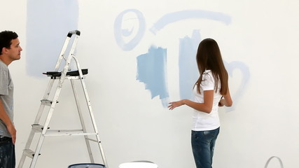 Woman drawing a heart on the wall
