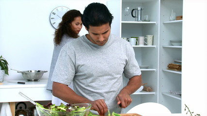 Concentrated man cutting vegetables with his girlfriend
