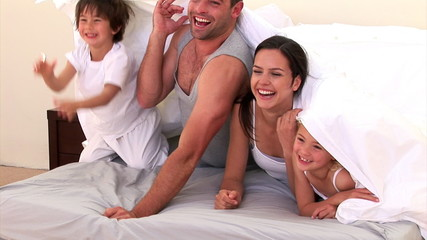 Adorable family hiding on the bed