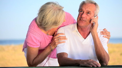 Affectionate Retired Couple Using Cell Phone