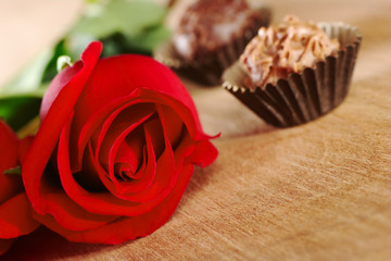 Red rose with two truffles on wooden board