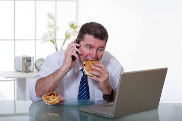 man at office with phone eat unhealthy food