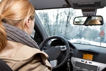 Junge blonde Frau fährt Auto im Winter