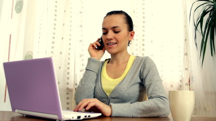 Woman talking on cellphone in front of the laptop
