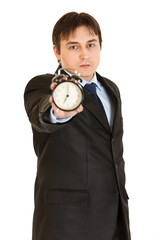 Serious young businessman holding alarm clock in hand