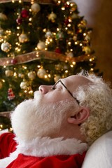 Santa Claus Asleep By The Christmas Tree