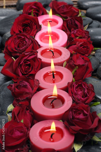 row of candles with red rose and stone