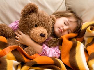 bimba che riposa  al caldo con l'orsacchiotto
