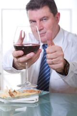 man with thumb up at restaurant with glass red wine