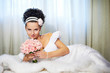 Beautiful bride with bouquet of flowers on white bed