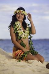 hula dancer sitting on the beach