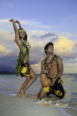 couple dancing hula by the ocean in hawaii