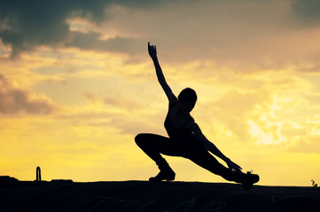 Silhouette of dancing woman over sunset. Yoga