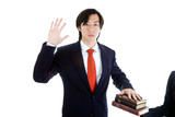 Serious Asian Business Man Swearing on Stack of Bibles, Isolated poster