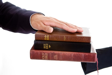 Man's Hand Resting on a Stack of Bibles, Isolated Background