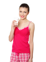 Young teen woman in pink pajama drinking milk