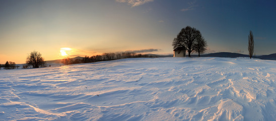 Sunset on frozen field with a chapel.
