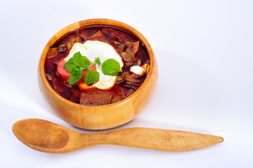 soup with sour cream in wood plate with spoon