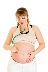 Surprised pregnant woman holding stethascope on her belly