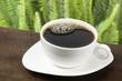 Taza blanca  con café tinto   en Fondo verde