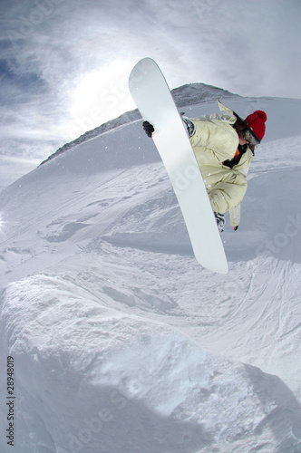 Jumping snowboarder in the mountains