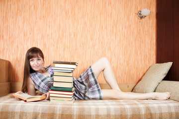 female student with books on sofa