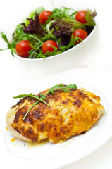 chicken breast baked in cheese and salad against white