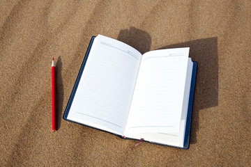 Notebook and pen isolated on desert