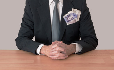 Man at desk with money, UK pounds, in pocket, hands clasped