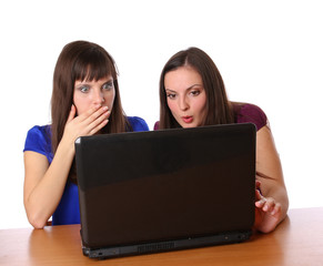 Two girlfriends looking at laptop