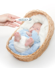 Newborn baby  in basket with temperature meter