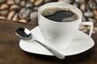 Taza de café blanca con granos de café de fondo