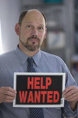 Businessman holding a Help Wanted sign