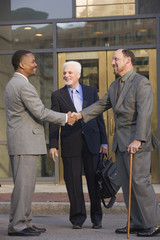 Three businessmen in front of their office building