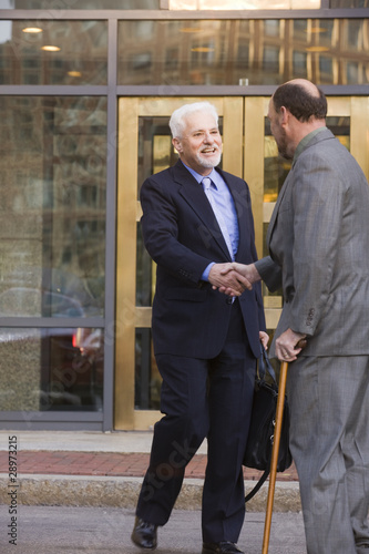 Two businessmen shaking hands in front of the bank