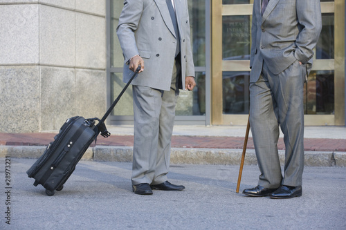 Two well dressed businessmen talking in front of office